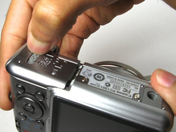 Image 1/2: On the bottom of the camera, use your thumb and push the battery lock up to open.  The battery compartment door should then spring open and batteries will slide out.