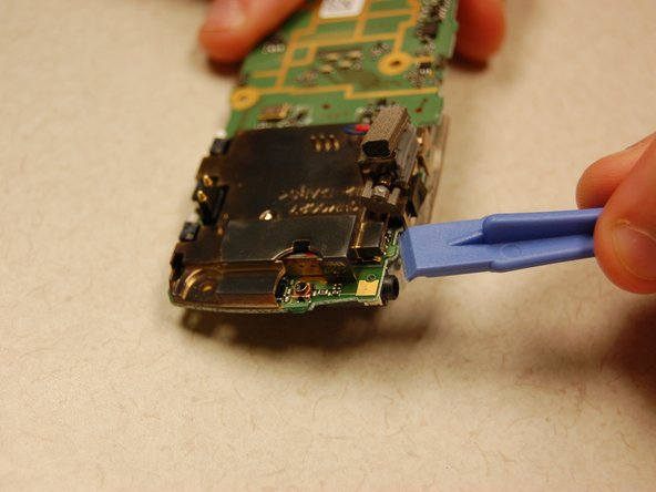Using the plastic opening tool, pull the white clips of the display away from the printed circuit board to unclip display.