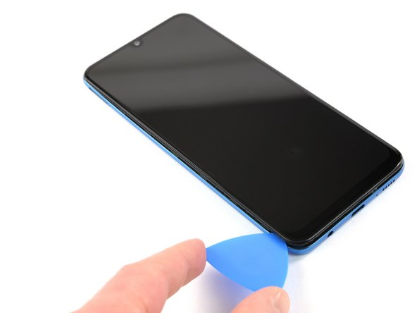 Continue sliding the pick along the left edge of the phone to release the clips.