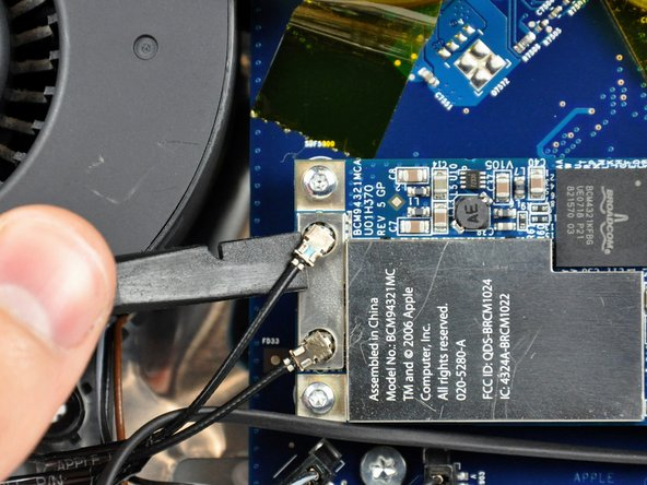 Image 1/2: Use the flat end of a spudger to pry both antenna connectors up off the AirPort Extreme card.
