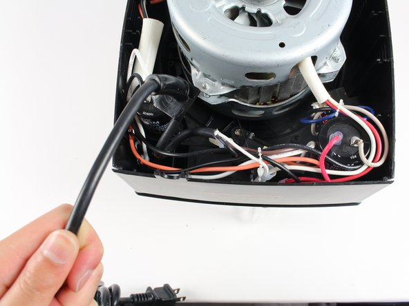Unlatch the power cord from its casing at the bottom left corner of the base by lifting the cord upward.