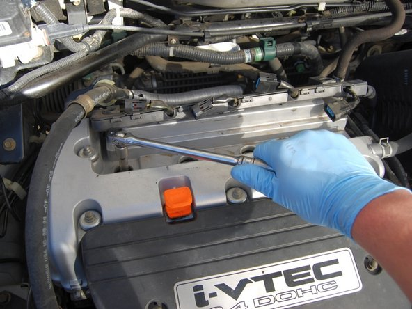Using the spark plug socket, put each spark plug into their hole and thread in hand tight.