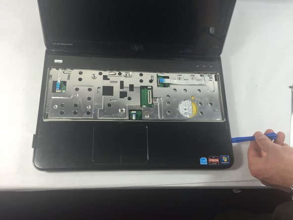 Use a plastic opening tool to carefully pry out the palmrest assembly and lift it off the computer base.