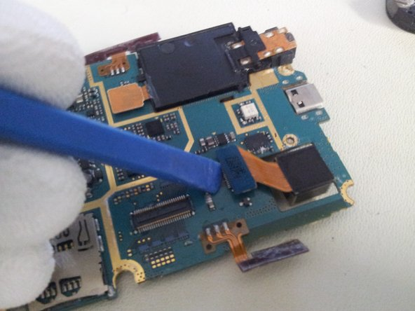 Use the removal tool to unclip the camera module from the Logic board.