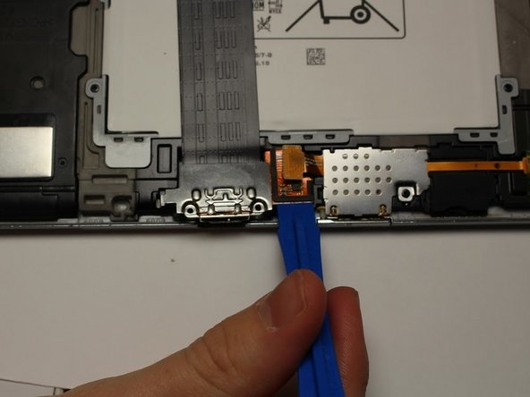 Using the plastic opening tool, carefully lift away the orange piece connected to the USB port.
