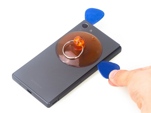 Place the suction cup to open a gap from top side, then insert guitar picks and slide it to cut the adhesive underneath.