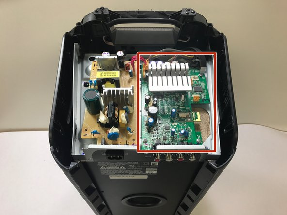 Find the large green motherboard, located underneath the top plastic housing of the speaker.