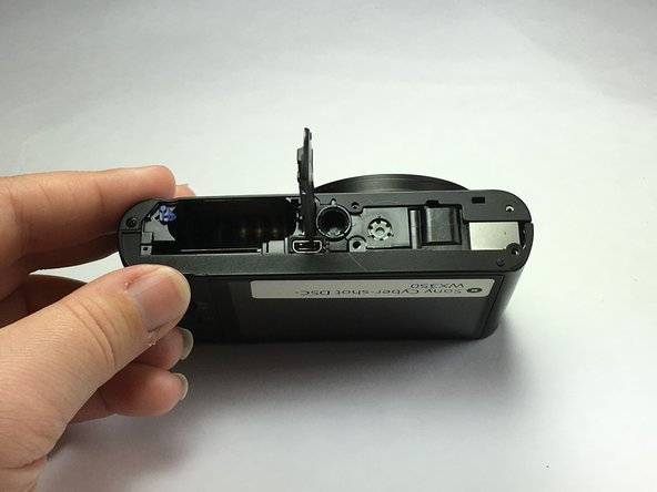 Push the piece towards the camera to separate it from the hinge.