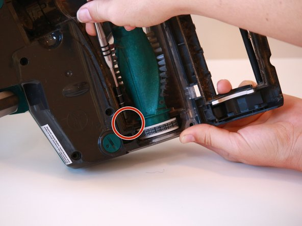 Remove the single 13.4 mm screw from behind the belted end of the roller brush with a T20 screwdriver bit.