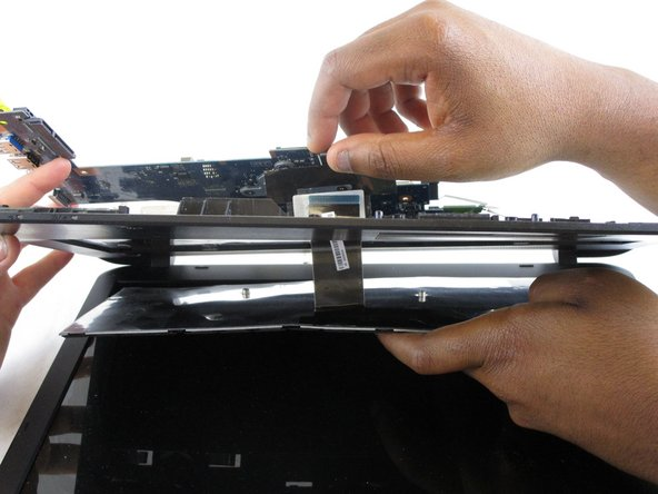 Slide the keyboard ribbon through its holding slot, completely releasing it from the laptop.