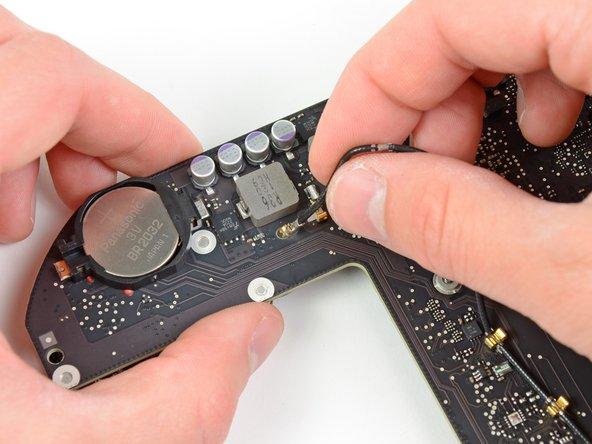 Fädle das Antennenkabel vorsichtig durch die Öffnung im Logic Board.