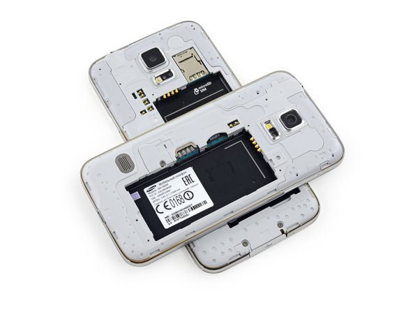 Spot the difference! When Samsung's wizards minimized the Galaxy S5, the SIM and microSD card slots migrated from their duplex to two individual units along the left edge of the battery compartment.