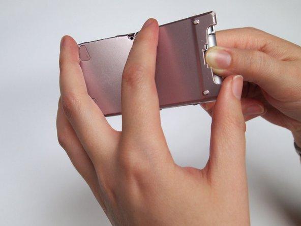 Tout en maintenant le bouton enfoncé, retirez le couvercle avec la main. Placez le pouce à l'arrière du téléphone.