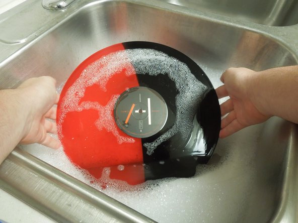 Put the record in the sink, submerging the record.
