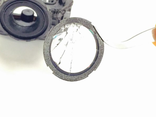 Use the plastic opening tool to gently pry the lens off of the camera.