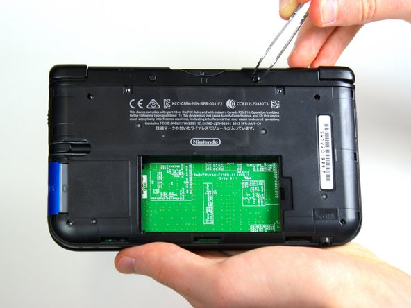 Using tweezers pull out the rubber bumpers that are located at the top of the device on either side of the game cartridge compartment.
