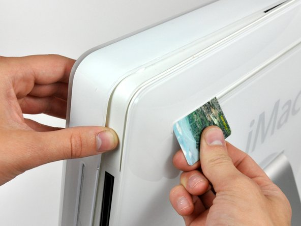 Insert a plastic card up into the corner of the air vent slot near the top of the rear case.