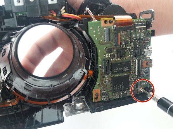 Using a PH000, unscrew the 3.5 mm screw on the bottom right side of the motherboard.