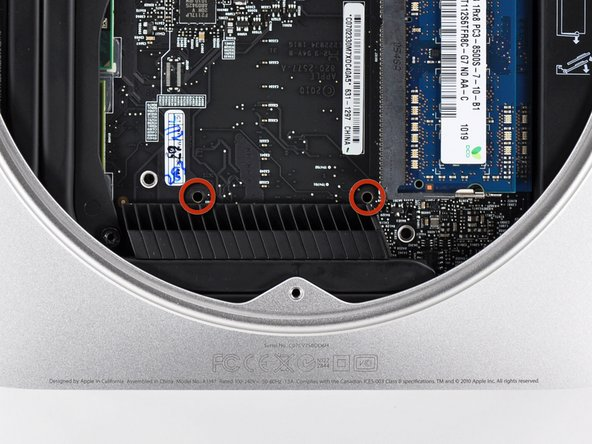 Image 1/3: Insert a [product|IF145-159|Mac Mini Logic Board Removal Tool] into the two holes highlighted in red. Be sure it makes contact with the outer case below the logic board before proceeding.