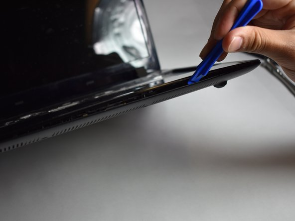Using a plastic opening tool, remove the top panel of the laptop.