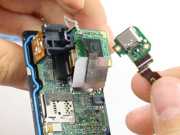 Once the ribbon cable is disconnected from the motherboard. The charging port assembly should come right off.