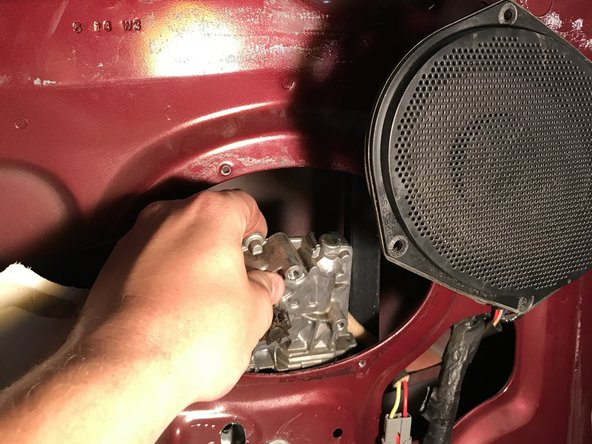 Reach inside the door panel and remove the existing motor.