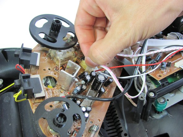 On the brown side of the quarter circle circuit board, remove the two white ribbon cables with pink stripes attached to a plastic connector. To do this, pinch the tabs with your hands while pulling outward on the connector.