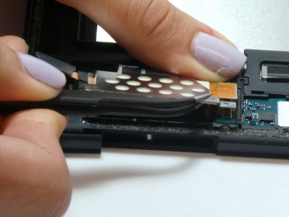 After Wiggled free place the tweezers on the piece of electrical tape connecting it to the device.