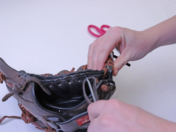 Using the Rawlings Glove Lacing Tool, start to weave the thread through the spot in the glove that needs repaired