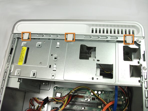 Locate the three plastic tabs connecting the computer's faceplate to the case.