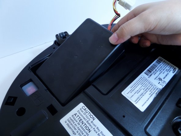 Lift the battery from the right side, up and out of its compartment.