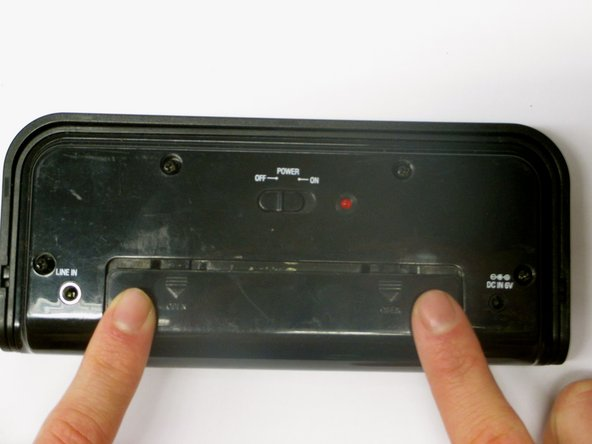 Use your fingers to slide the battery case cover off in the direction of the arrows.