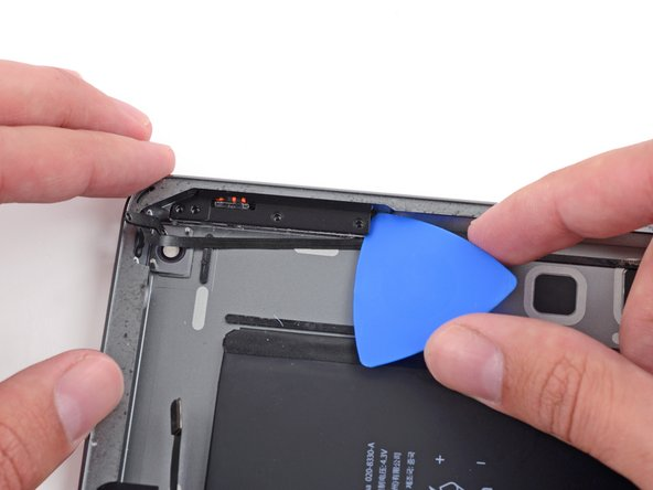 Insert an opening pick under the far right corner of the button bracket, between it and the rear case.