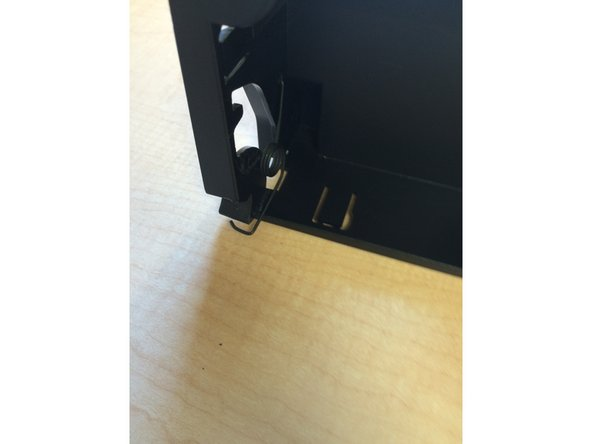Remove the spring located in the back part of the cup holder by pinching the end nearest you by moving it up and down and in and out-of-place