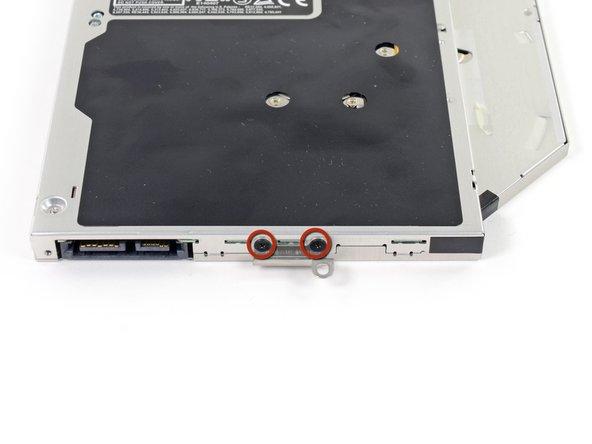 Entferne die beiden schwarzen Kreuzschlitzschrauben Größe #0, die die kleine Metallöse am Laufwerk befestigen.
