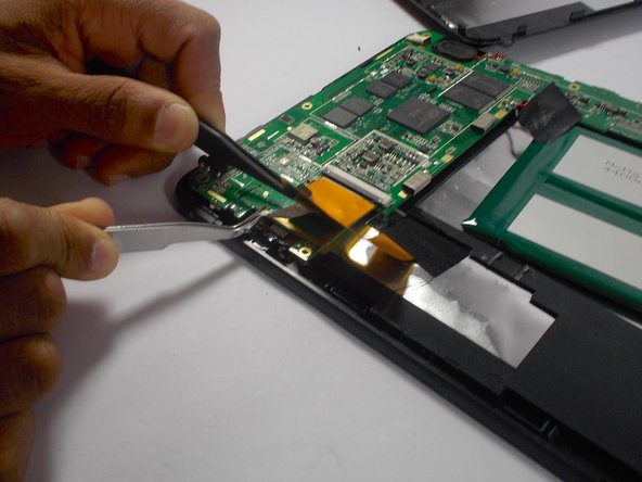 Image 1/3: Use a second pair of tweezers to pull the gold tab connected to the camera out of the circuit board.