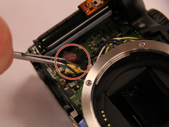 On the lower left side on the front of the camera, disconnect the red and yellow wires from the circuit board.