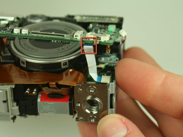 Image 2/3: Locate the white ribbon cable attached to the underside of the main circuit board.