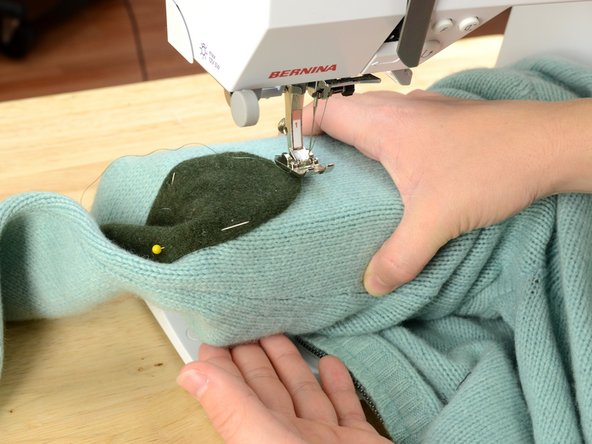 You may need to remove the table from your sewing machine to allow the sweater sleeve to slide over the sewing machine arm. Check you sewing machine manual for specific instructions on your machine.