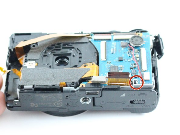 The mainboard is held in place by the marked locking tang.  Using your fingers, push the locking tang away from the mainboard.  If you cannot push with your fingers, a plastic spudger can be used instead.