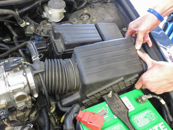 Next, separate the air filter housing from the bottom of the housing. To do this, with both hands, grab the Air Filter Housing from the exterior and push towards the engine block while pulling up.