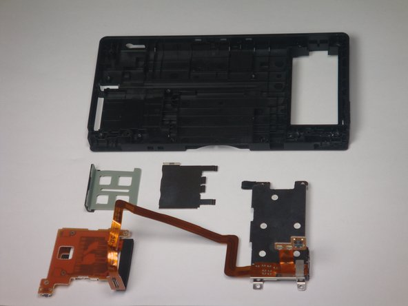 This picture shows the  LCD screen, battery compartment, and SD card slot (metal shield and flap) with bottom outer casing.