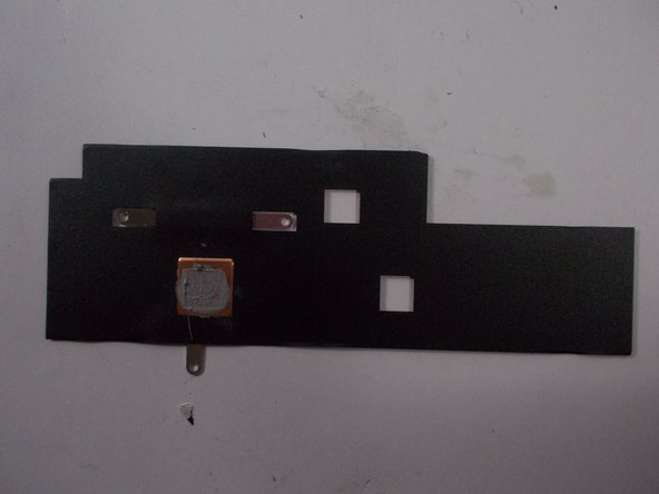 Image 2/2: Place the heat sink down elsewhere with the black underside facing up.