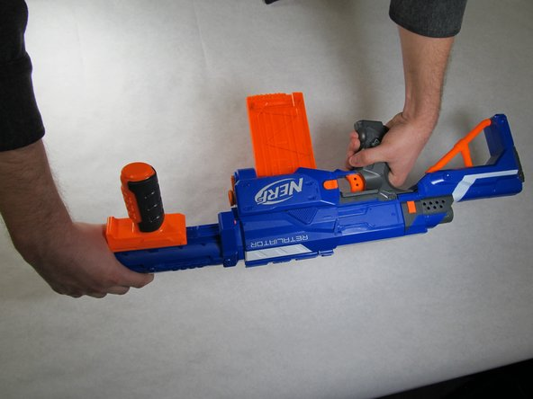 While holding the blaster, rotate the barrel assembly in the counter-clockwise direction and pull away from the blaster.