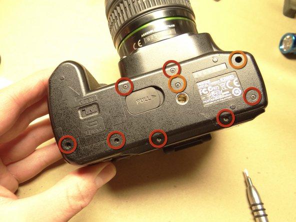 下部カバーとカメラボディを固定する7本のネジ(赤丸、4.3 mmプラスネジ)を取り外します。