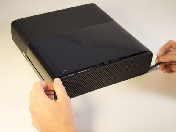 Slide the spudger along the separation you have created between the grated panel and the bottom body of the Xbox.