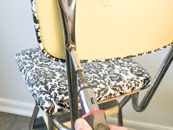 Using a Phillips #0 screwdriver, unscrew the back rest from the stool.