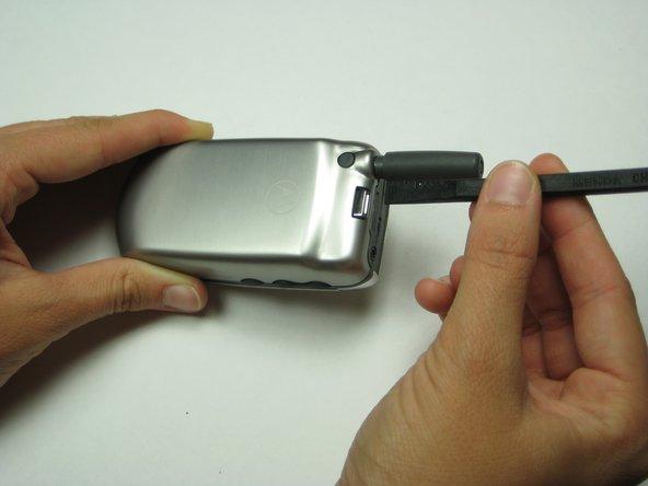 En utilisant soit vos doigts ou un outil de type spugder, appuyez sur le bouton situé près du haut du téléphone, près de l'antenne.