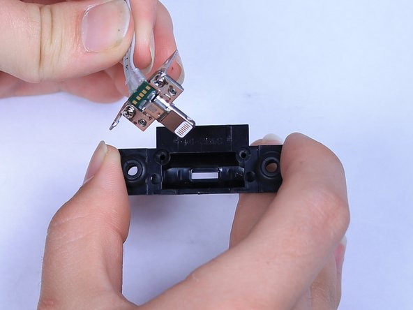 Remove the metal frame around the lightning connector from its plastic cover.