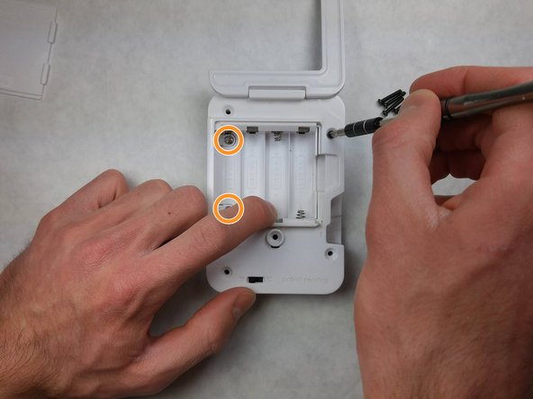 Remove two silver-colored 5 mm Phillips screws from the left side of the internal cover.